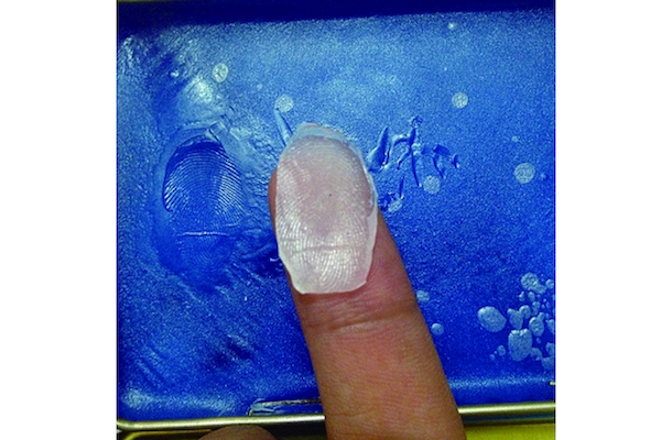 A screenshot shows a Chinese journalist making a fake fingerprint by using a fingerprint membrane maker ordered on the Internet. (Legal Evening News/Screenshot/Epoch Times)