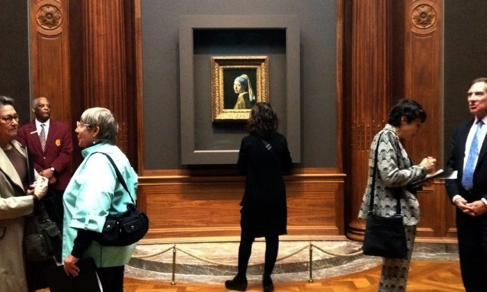 """Reporters at the press preview of the Frick's Collection's newest exhibit, on loan from the Mauritshuis in The Hague. Vermeer's """"Girl with a Pearl Earring"""" is a familiar face welcoming visitors to discover more Dutch masterworks. (Christine Lin/Epoch Times)"""