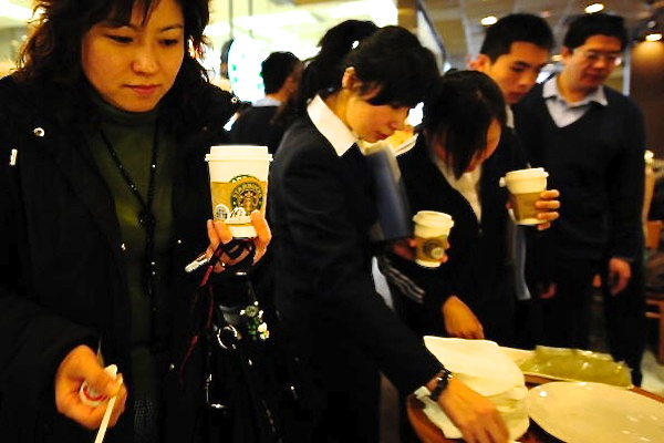Customers get coffee at a Starbucks store in Beijing on Jan. 14, 2009. Party mouthpiece CCTV criticizes Starbucks for being too expensive in coordinated reports on Oct. 20 and 21. (Frederic J. Brown/AFP/Getty Images)