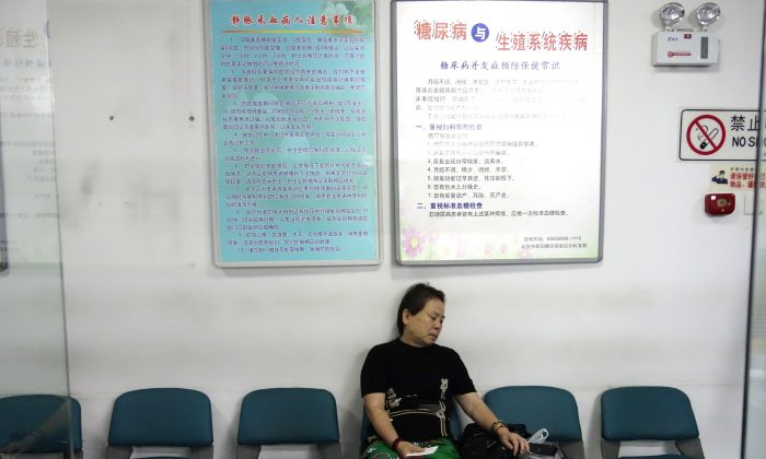 A woman waits to receive treatment as she sits in front of a billboard showing how to avoid diabetes at a diabetes hospital in Beijing on Sep. 4, 2013. Almost 12 percent of adults in China had diabetes in 2010, a slightly higher proportion than in the United States. (Wang Zhao/AFP/Getty Images)