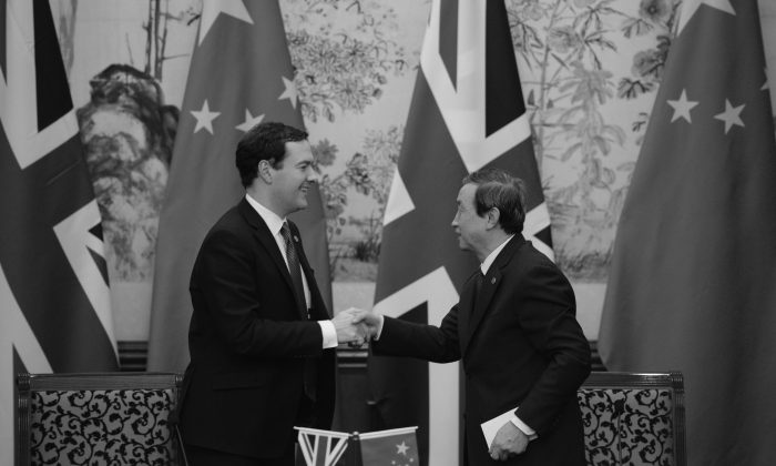 Britain's Finance Minister George Osborne (L) shakes hands with Chinese Vice Premier Ma Kai (R) during a signing ceremony at Diaoyutai Guesthouse in Beijing on Oct. 15. Analysts thought that China did well in its dealings with the United Kingdom recently. (Kota Endo/AFP/Getty Images)