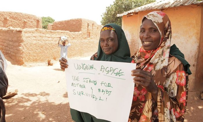 """Women holding a sign saying """"We stand for mother & baby survival!"""" in Katsina, northern Nigeria. (Courtesy of Okikiola Akinkugbe)"""