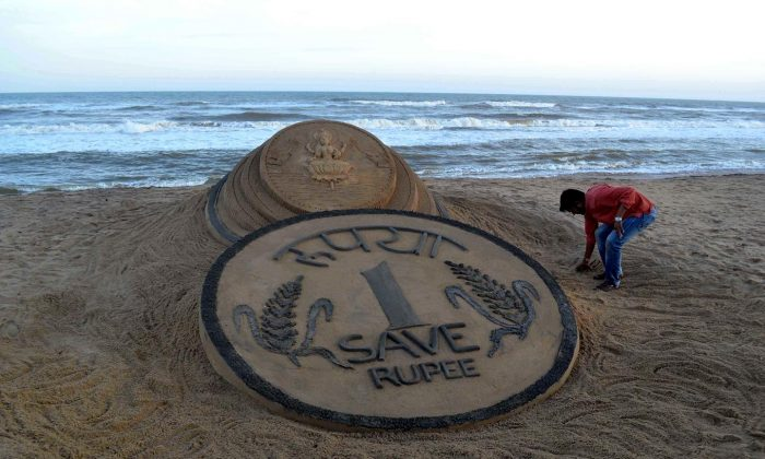 Indian sand artist Sudarsan Pattnaik puts the finishing touches to his sand sculpture of a rupee coin in front of a Hindu Goddess on the beach at Puri, some 65km from Bhubaneswar on August 22, 2013. The rupee, which has hit record low against the U.S. dollar has not deterred those with dreams to go abroad as the returns on investment have also increased manifold times. (Strdel/AFP/Getty Images)