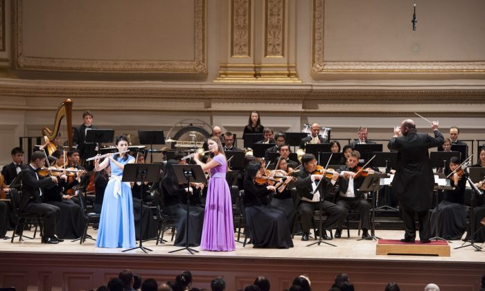 """Chia-Jung Lee (L) and Lana Kuscer (R) perform A.B. Furstenau's """"Rondo Brillant for Two Flutes and Orchestra, Op.102"""" in the Shen Yun Symphony Orchestra at Carnegie Hall in New York City on Oct. 5, 2013.  Lana Kuscer has performed solo performances for the U.K Houses of Parliament and for U.K. royal family. (Dai Bing/Epoch Times)"""