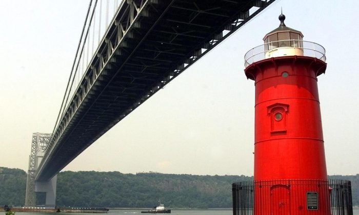 """The Jeffrey Hook Lighthouse, which is also called Little Red Lighthouse, sits on the edge of Manhattan Island beneath the span of the George Washington Bridge along the Hudson River in New York, 19 July, 2002. The Little Red Lighthouse Festival this Saturday includes a tour of the lighthouse, readings from the children's book """"The Little Red Lighthouse and the Great Gray Bridge,"""" fishing clinics, live entertainment, food vendors, and other activities at this annual festival. (Matt Campbell/AFP/Getty Images)"""