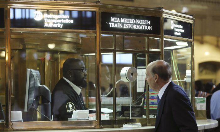 A Metro-North customer service agent helps a morning rush-hour commuter with train information at Grand Central Terminal in New York City, Sept. 26, 2013. (Mary Altaffer/AP Photo)