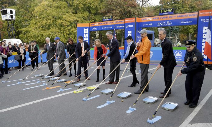 VIPs and officials, including Mary Wittenberg, New York Road Runners president and CEO (5th L), and Thomas Grilk, executive director of the Boston Athletic Association (6th L), participates in the ceremonial painting of the finish line of the NYC Marathon in Central Park, Oct. 30, 2013. (Seth Wenig/AP)