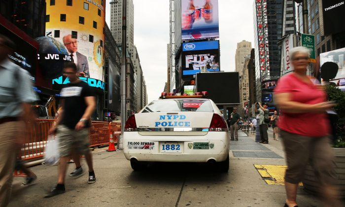 People walk by a New York Police Department car in Times Square, New York, August 12, 2013. (Spencer Platt/Getty Images)