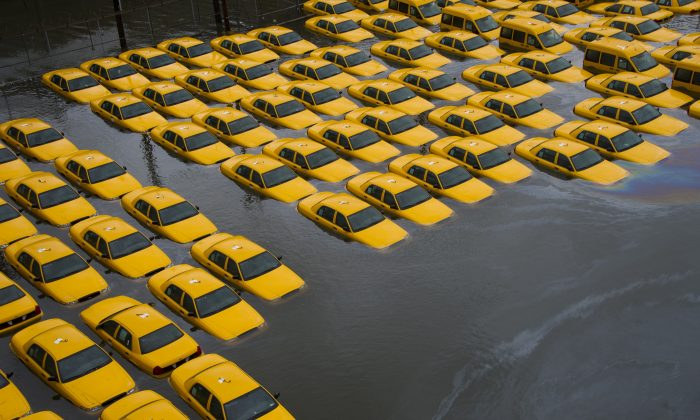 A parking lot full of yellow cabs is flooded as a result of Superstorm Sandy, in Hoboken, N.J., Oct. 30, 2012. (AP Photo/Charles Sykes)