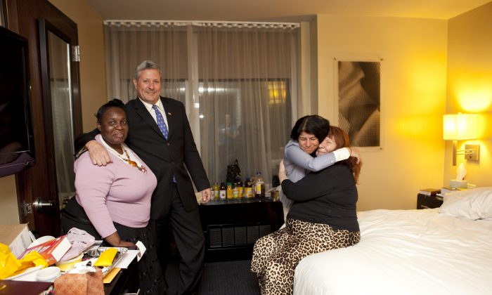 Sandy evacuees (L-R) Jocelyne Oscar, John Finan, Rachal Azani, and Joan Sweet share a happy moment in Sweet's hotel room at the Hilton Hotel in Manhattan after hearing that an anonymous donor saved them from living on the streets. (Samira Bouaou/Epoch Times)