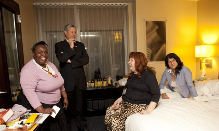 Sandy evacuees (L-R) Jocelyne Oscar, John Finan, Rachal Azani and Joan Sweet share a happy moment in Sweet's hotel room at the Hilton Hotel in Manhattan after hearing that an anonymous donor saved them from living on the streets. (Samira Bouaou/Epoch Times)
