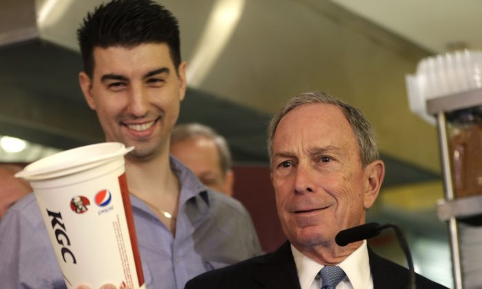 New York City Mayor Michael Bloomberg looks at a 64oz cup, as Lucky's Cafe owner Greg Anagnostopoulos (L), stands behind him. (Seth Wenig/AP)