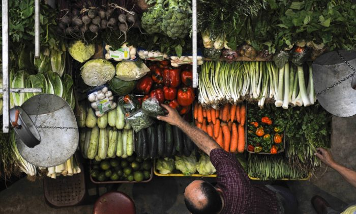 A man buys vegetables in a public market in Caracas, Venezuela, on May 6, 2011. A Venezuelanalysis article published in October 2013 looks at the facts and the myths behind the media hype over Venezuelan foot shortages this year. (Leo Ramirez/AFP/Getty Images)