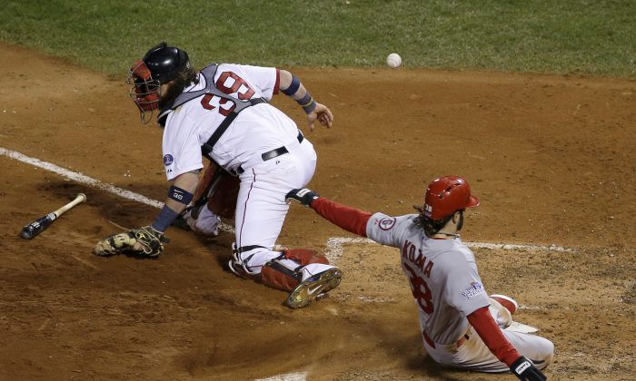 St. Louis Cardinals' Pete Kozma scores on a sacrifice fly as Boston Red Sox catcher Jarrod Saltalamacchia can't handle the throw during the seventh inning of Game 2 of baseball's World Series Thursday, Oct. 24, 2013, in Boston. (AP Photo/Matt Slocum)