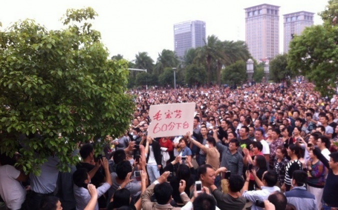 "In eastern China's Zhejiang Province tens of thousands of protesters gather in front of the Yuyao City government building on Oct. 15, 2013. A banner held by protesters says ""60 Point Mao Hongfang, Step Down."" (Weibo.com)"