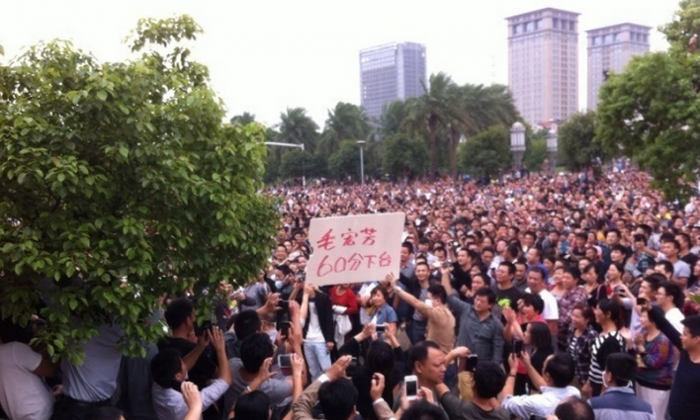"""Yuyao-protest: Tens of thousands of protesters gather in front of Yuyao City government building on Oct. 15. A banner held by protesters says """"60 Point Mao Hongfang, Step Down."""" (Weibo.com)"""