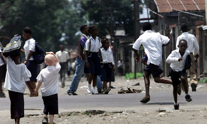 A young girl holds the hand of an albino boy as two other boys run across a road on their way back from school in Kinshasa, capital of Congo, Thursday Jan. 25, 2001. An article published in All Africa in October 2013 looks at the hardships an albino boy faces in the country, where the organs of albinos are hunted for witchcraft. (AP Photo/Christine Nesbitt)