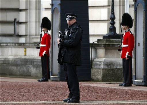 A British police officer guards the grounds of Buckingham Palace in central London, Monday, Oct. 14, 2013, after British police arrested a man, David Belmar, with a knife after he tried to dart through a gate at Buckingham Palace in London on Monday. The palace said Queen Elizabeth II was not in residence. Breaches of royal security are rare, but just a month ago police arrested two men over a suspected break-in at the palace. (AP Photo/Lefteris Pitarakis)