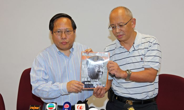 Lawyer Albert Ho (L) and iSun Affairs Weekly editor Zhang Meng (R) stand holding a copy of the magazine containing the interview with Lew Meng-hong that Hong Kong's Independent Commission Against Corruption (ICAC) wished to gain information about. On Oct. 7 in the High Court the ICAC withdrew its request. (Pan Zaishu/Epoch Times)