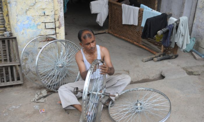 Indian laborer, Lala, adjusts the spokes of a bicycle wheel at a roadside shop in the old section of New Delhi on July 20, 2011. Majority of entrepreneurs feel that misuse of SAFTA by countries like China is inflicting a potential damage on the local industry and bringing it to the back foot. (Sajjad Hussain/AFP/Getty Images)