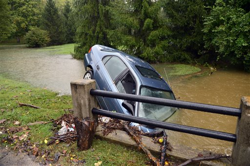 A car is upended in a creek in the 3300 Blk. of Ten Broeck Way, in Louisville, Ky.,, appearing to have driven off the roadway during flooding conditions on Sunday, Oct. 6, 2013. Dozens of people in homes hit by flooding of low-lying areas around Louisville and Jefferson County had to be evacuated overnight, some by rescue personnel using boats, authorities said Sunday. (AP Photo/The Courier-Journal, Scott Utterback)