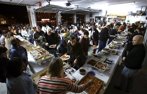 People enjoy a pot luck dinner in Sea Bright fire department in Sea Bright, N.J., Oct. 29, 2013, as residents  marked the one-year anniversary of Superstorm Sandy. (AP Photo/Mel Evans)