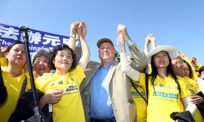 Congressman Dana Rohrabacher holds hands with Falun Gong practitioners during a rally calling for an end to the persecution to Falun Gong in China, at Long Beach in Los Angeles on Oct. 20. (Song Xianglong/Epoch Times)