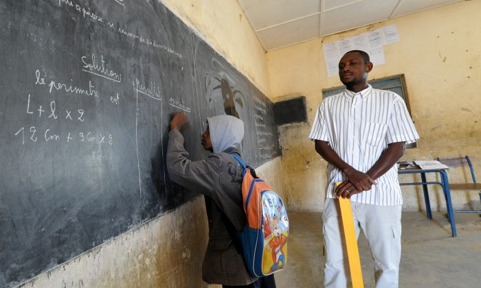 A student writes at the blackboard as the teacher looks on in a classroom in Gao, in the north of Mali, on the first day of the reopening of schools after the French bombing of Islamist targets, on Feb. 4, 2013. (Sia Kambou/AFP/Getty Images)
