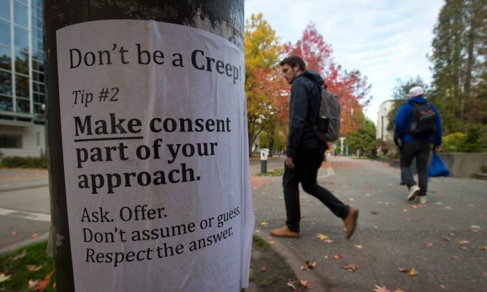University of British Columbia students walk past a sexual assault poster on campus on October 30, 2013. The RCMP is investigating six sex assaults that occurred at UBC since April. (The Canadian Press/Darryl Dyck)