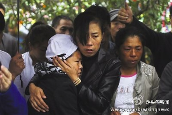 Vendor Xia Junfeng's wife (c) and son attend Xia's funeral at Memorial Forest Cemetery at suburb of Shenyang City on Oct. 1. (Weibo.com)