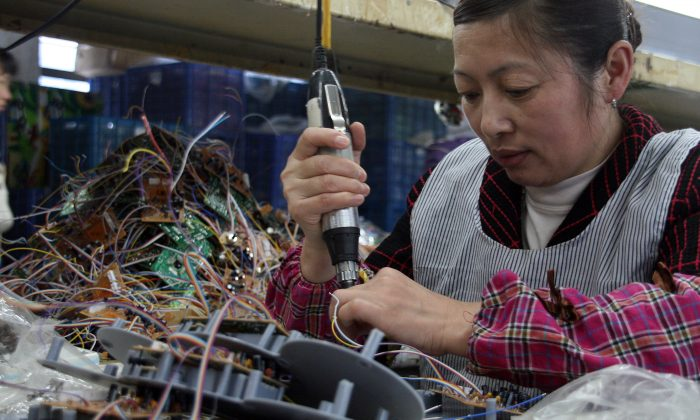 In this file photo a woman is at work in a factory in southeast China's Fujian Province on April 2, 2011. Even the simplest electronic appliances made in China may come with a surprise—a device intended to enable cyber crime. (STR/AFP/Getty Images)