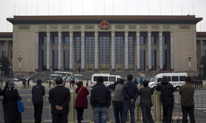 """People watch as police officers check visitors in front of the Great Hall of the People during a gathering of the 205-member Central Committee's third annual plenum in Beijing, China Saturday, Nov. 9, 2013. The watchword for the Chinese Communist Party's Third Plenum of the 18th Central Committee has been """"reform."""" (AP Photo/Andy Wong)"""