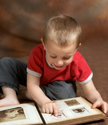 A file photo of a boy looking through an old photo album. A boy called Sam in case studies made some startling statements while looking through old family photos, cited as evidence along with numerous other cases of reincarnation. (Shutterstock*)