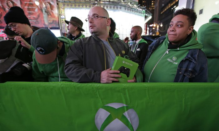 People line up outside the Best Buy Theater in Times Square awaiting the opportunity to purchase Microsoft's Xbox One video gaming console at a midnight sales launch, Thursday, Nov. 21, 2013, in New York. (AP Photo/Kathy Willens)