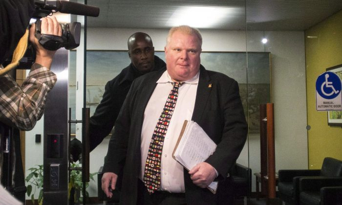 Mayor Rob Ford arrives at city hall in Toronto on Nov. 19, 2013. Newly released documents say police overheard alleged gang members on wiretaps talking about delivering drugs to Ford and having pictures of him using drugs, suggesting the images could be used for blackmail. (The Canadian Press/Chris Young)
