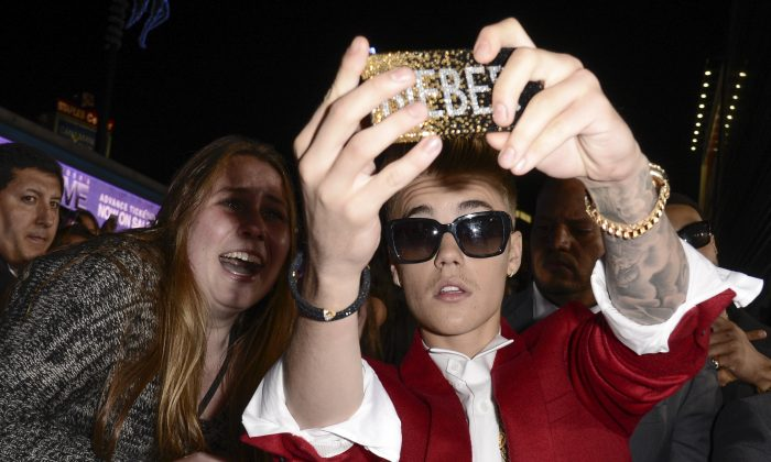 """In this Dec. 18, 2013 file photo, singer Justin Bieber takes a """"selfie"""" with a fan at the premiere of the feature film """"Justin Bieber's Believe"""" at Regal Cinemas L.A. Live  in Los Angeles. (AP Photo/Dan Steinberg, Invision)"""