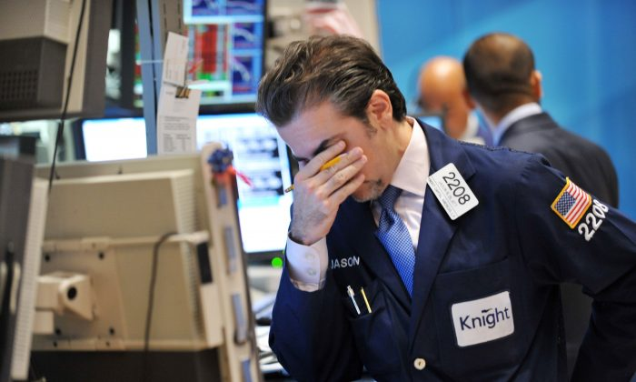 A trader for Knight Capital reacts to a down market on the floor of the New York Stock Exchange, Aug. 8, 2011. The company's algorithmic trading desk suffered heavy losses in 2012, illustrating the broader risk high-frequency trading poses to the markets. (Stan Honda/AFP/Getty Images)