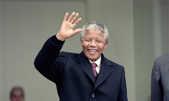 Nelson Mandela waves to the press as he arrives at the Elysee Palace, 07 June 1990, in Paris, to have talks with French president Francois Mitterrand. (Michel Clement, Daniel Janin/AFP/Getty Images)