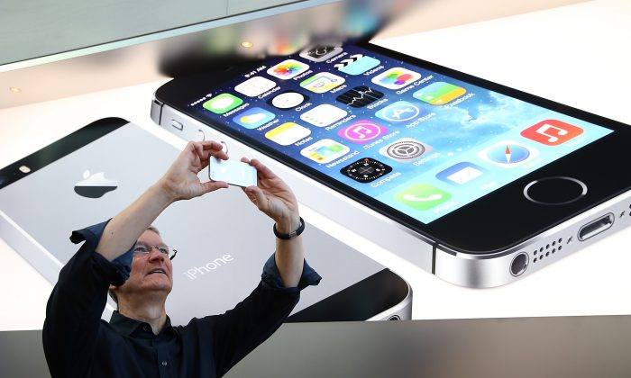 Apple CEO Tim Cook takes pictures in Palo Alto, Calif., Sept. 20 2013. Apple's iPhone 6 might feature a larger screen, according to rumors. (Justin Sullivan/Getty Images)