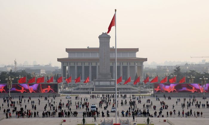 """Tourists visit Tiananmen Square on Nov. 14, 2013, in Beijing, China. On Jan. 23, 2001, the Chinese regime staged """"self-immolations"""" by alleged Falun Gong practitioners and then featured video of the fabricated event in propaganda attacking the group. (Feng Li/Getty Images)"""