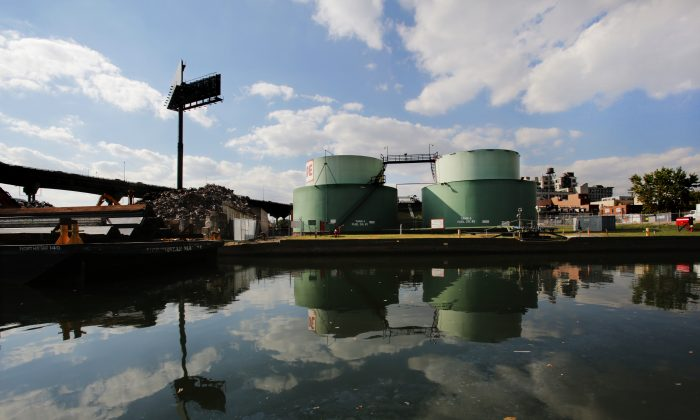 Oil storage tanks are reflected in the Gowanus Canal in Brooklyn, New York, Sept. 30, 2013. (Mark Lennihan/AP)