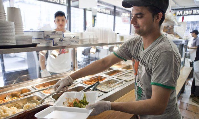 A man serves a customer at a buffet in Midtown Manhattan, New York, Sept. 12. (Samira Bouaou/Epoch Times)