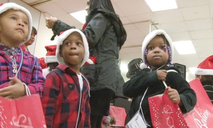 """Children hold their Macy's shopping bags during """"Operation Happy Children"""" at the Macy's store in Manhattan, New York, Dec. 3, 2013. (Seth Hirsch)."""