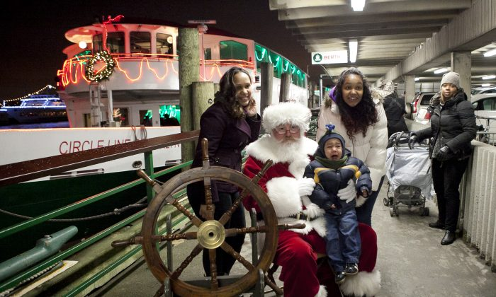 Santa poses with one of the last children in line to a holiday cruise boat at Pier 81 in Manhattan, New York, Dec. 9, 2013. (Samira Bouaou/Epoch Times)
