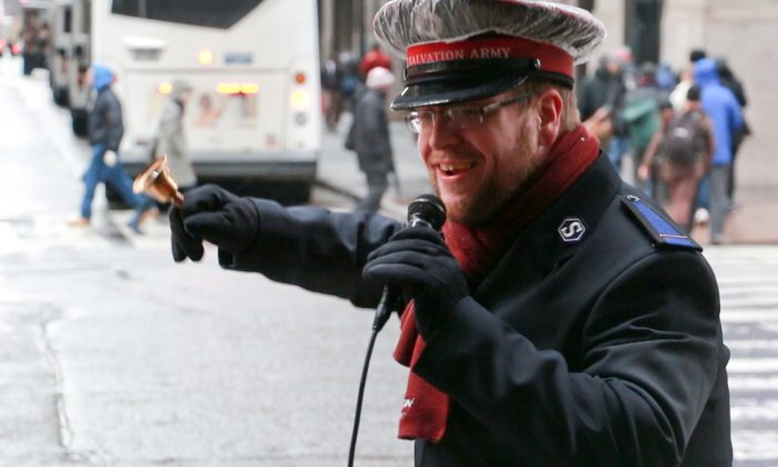 Michael Buzzard rings and sings outside New York Penn Station on Dec. 10, 2013. (Allen Xie)