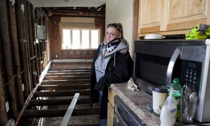 Stacey Walsh in her home in Broad Channel, Queens. About seven months after Sandy, she was seriously injured in a car crash that left her in a neck brace. (Samira Bouaou/Epoch Times)