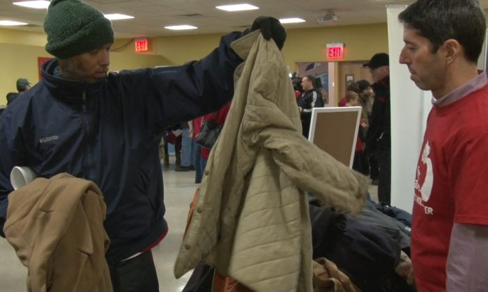 A New York Care volunteer helps a people pick out a warm winter coat at the New York City Rescue Mission, Dec. 25. (Oliver Trey)