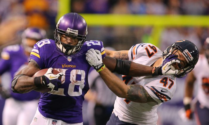 Adrian Peterson #28 of the Minnesota Vikings carries the ball for ten thousand career rushing yards against Chris Conte #47 of the Chicago Bears on December 1, 2013 at Mall of America Field at the Hubert Humphrey Metrodome in Minneapolis, Minnesota. (Photo by Adam Bettcher/Getty Images)