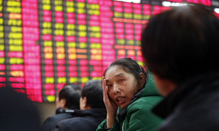 An investor chats  with another at a private securities company on Tuesday, Dec. 24, 2013 in Shanghai, China.  (AP Photo)