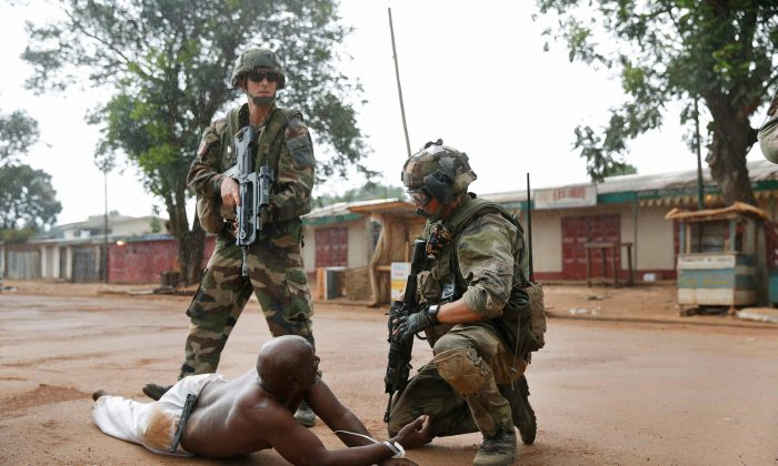 French troops detain a suspected Seleka officer, preventing Christian mobs from lynching him near in Bangui, Central African Republic, Dec. 9, 2013. (AP Photo/Jerome Delay)